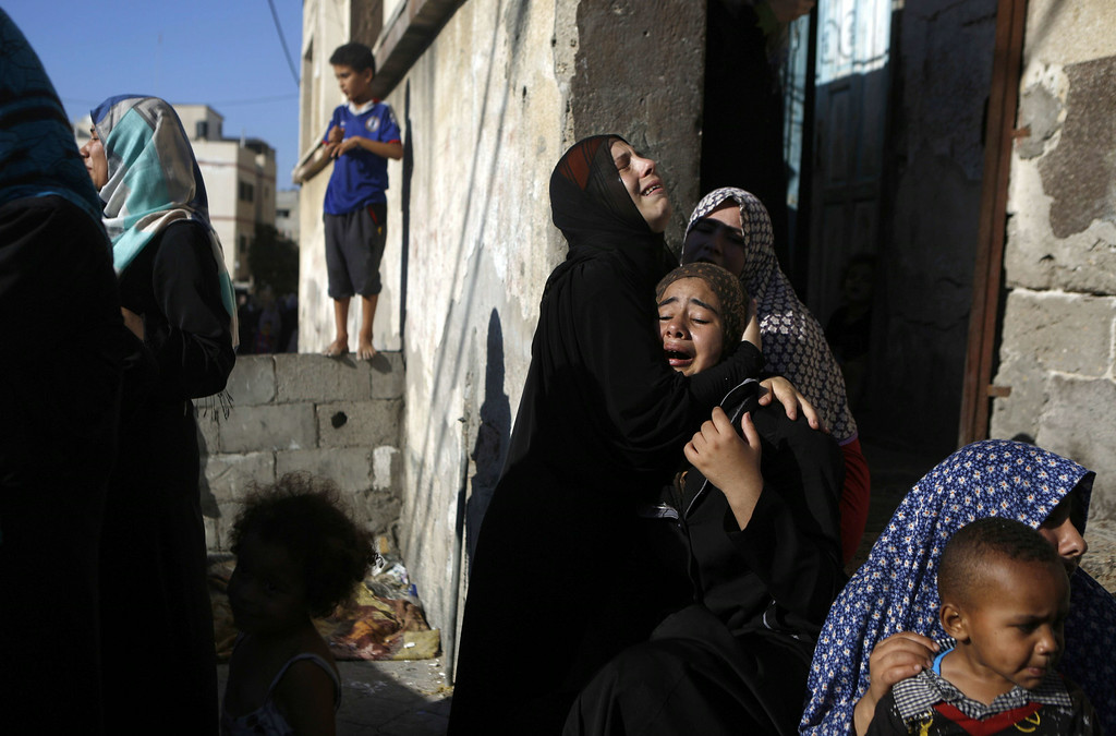 Description of . Palestinian women react during the funeral of four boys, all from the Bakr family, killed during Israeli shelling, in Gaza City, on July 16, 2014. Four children were killed and several injured at a beach in Gaza City medics said, in Israeli shelling witnessed by AFP journalists. The strikes appeared to be the result of shelling by the Israeli navy against an area with small shacks used by fishermen. The deaths raised the overall toll in nine days of violence in Gaza to 213. AFP PHOTO / MOHAMMED ABED/AFP/Getty Images