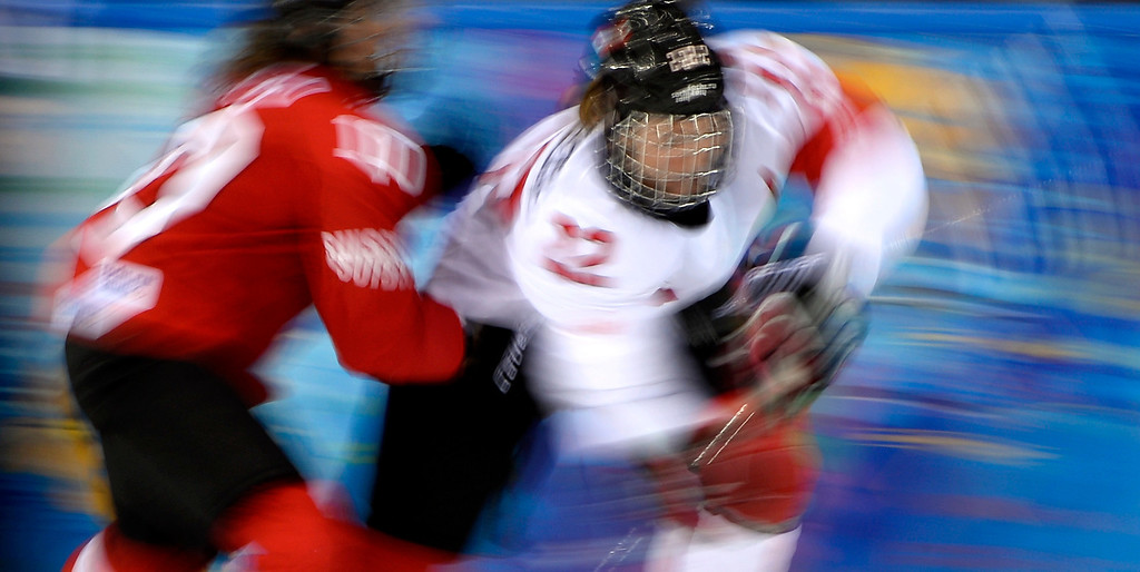 Description of . Canada's Hayley Wickenheiser (R) vies with Switzerland's Nicole Bullo during the Women's Ice Hockey semifinal match Canada vs Switzerland at the Shayba Arena during the Sochi Winter Olympics on February 17, 2014. Canada won 3-1.    DJONATHAN NACKSTRAND/AFP/Getty Images