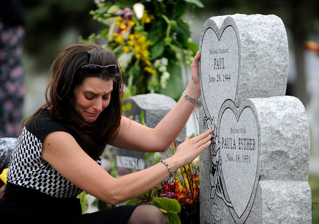Description of . Andrea Sandoval Reed, grieves at her father's headstone at Mt. Olivet Cemetery during burial services. Andrea's father, Paul Sandoval, a former Colorado State Senator, passed away April 24th, 2012 after a battle with pancreatic cancer. Andy Cross, The Denver Post