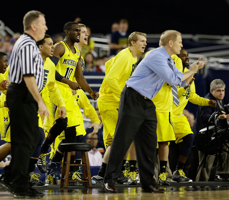 Description of . The Michigan bench reacts during the second half of a regional semifinal game against Kansas in the NCAA college basketball tournament, Friday, March 29, 2013, in Arlington, Texas. (AP Photo/Tony Gutierrez)