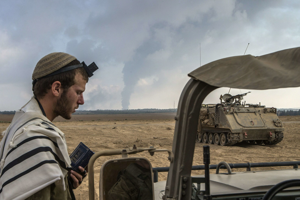 Description of . An Israeli soldier prays on the Israeli side of the border with the Gaza Strip, on July 29, 2014, as smoke billows from a power plant following overnight Israeli shelling in the coastal Palestinian enclave. The only power plant supplying electricity to the Gaza Strip was knocked out of commission by Israeli shelling, deputy director of the energy authority in the Palestinian territory said. AFP PHOTO / JACK  GUEZ/AFP/Getty Images