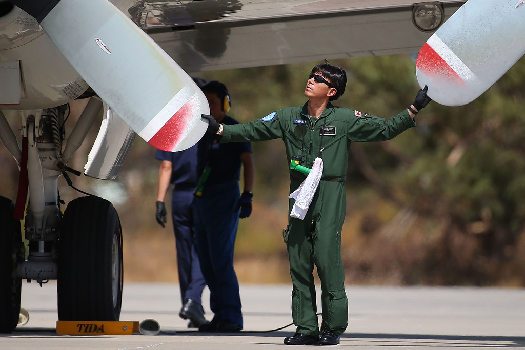 Description of . A Japanese Maritime Self Defence Force member inspects a P-3C Orion prior to departure from the RAAF base Pearce in Bullsbrook, 35 kms north of Perth, on March 24, 2014 to search for missing Malaysia Airlines flight MH370 over the southern Indian Ocean. AFP PHOTO / POOL / Paul Kane/AFP/Getty Images