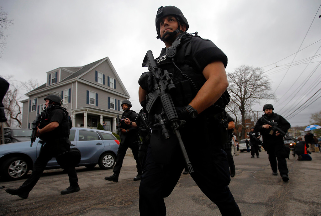 Description of . Police officers search house to house for the second suspect in the Boston Marathon bombings in a neighborhood of Watertown, Massachusetts April 19, 2013.  Black Hawk helicopters and heavily armed police descended on a Boston suburb Friday in a massive search for an ethnic Chechen suspected in the Boston Marathon bombings, hours after his brother was killed by police in a late-night shootout.     REUTERS/Brian Snyder