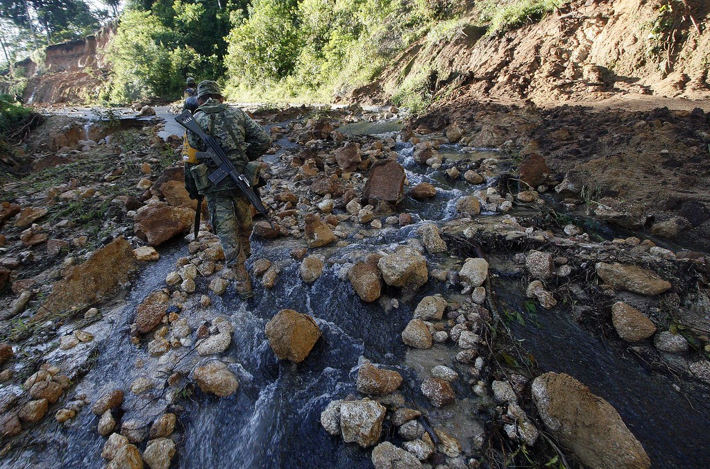 Description of . Mexican soldiers walk along a damaged road to bring relief aid to La Pintada, state of Guerrero, Mexico, on September 19, 2013 as heavy rains hit the country. AFP PHOTO/Pedro PARDO/AFP/Getty Images