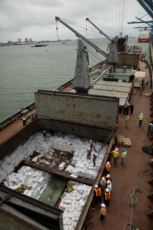 Description of . Panamanian workers stand atop sacks of sugar inside a container aboard a North Korean-flagged ship at the Manzanillo International container terminal on the coast of Colon City, Panama, Tuesday, July 16, 2013. (AP Photo/Arnulfo Franco)