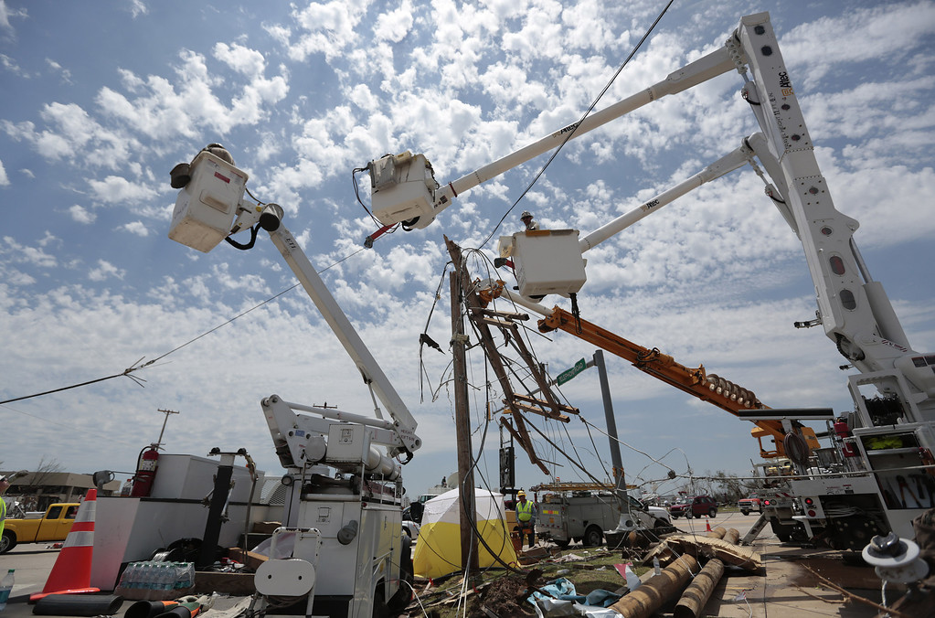 Description of . MOORE, OK -  MAY 23:   Electrical crews begin to replace power lines after the May 20 tornado May 23, 2013  in Moore, Oklahoma. The tornado of at least EF4 strength and up to two miles wide touched down May 20 killing at least 24 people and leaving behind extensive damage to homes and businesses. U.S. President Barack Obama promised federal aid to supplement state and local recovery efforts.    (Photo by Brett Deering/Getty Images)