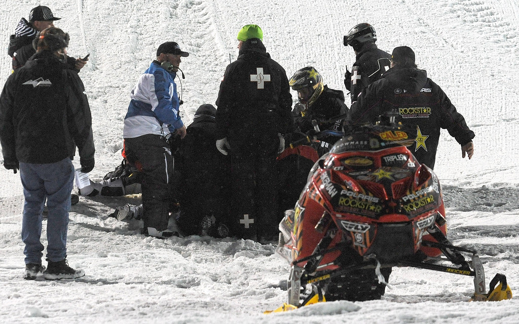 Description of . In this photo taken Jan. 24, 2013, emergency personnel tend to Caleb Moore after he crashed during the snowmobile freestyle event at the Winter X Games in Aspen, Colo.  (AP Photo/The Colorado Springs Gazette, Christian Murdock)