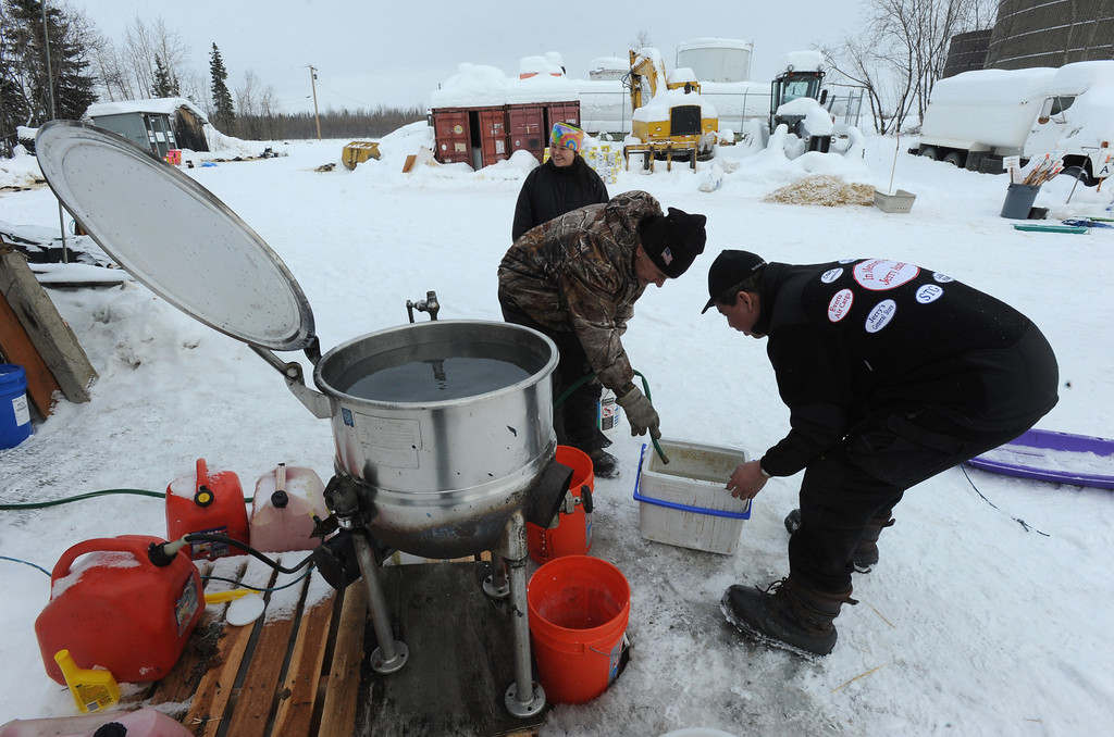 Description of . Musher Louie Ambrose gets hot water at the Iditarod checkpoint in McGrath on Wednesday, March 6, 2013, at Nikolai Airport in Nikolai, Alaska. (AP Photo/The Anchorage Daily News, Bill Roth)