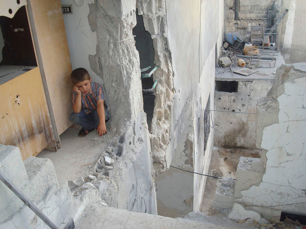 Description of . A boy sits at his parents' house, damaged by shelling by forces loyal to Syria's President Bashar al-Assad, in Talbiseh, near Homs August 31, 2012.   REUTERS/Shaam News Network/Handout