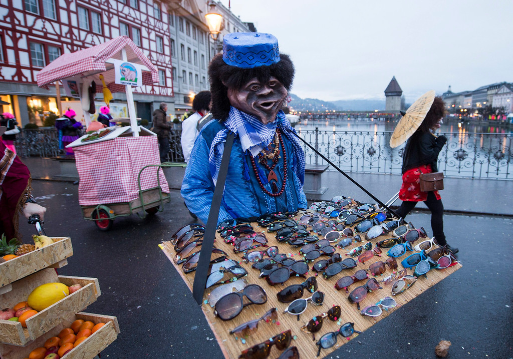Description of . A carnival character in full costume walks with a tray of sunglasses as he arrives  to take part in a procession through the historic centre of Lucerne, Switzerland 27 February 2014 at the start of the annual traditional Fasnacht (Carnival) celebrations.  EPA/SIGI TISCHLER