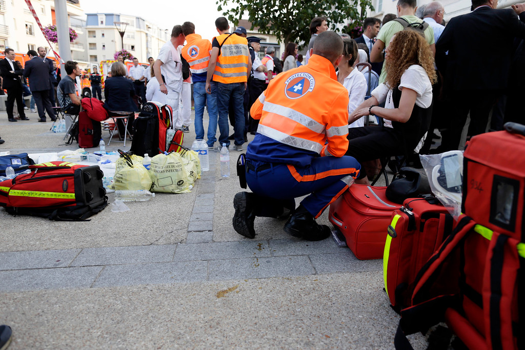Description of . Rescue workers tend to victims at the site of a train accident in the railway station of Bretigny-sur-Orge, Friday, July 12, 2013 near Paris. (AP Photo/Kenzo Tribouillard, Pool)
