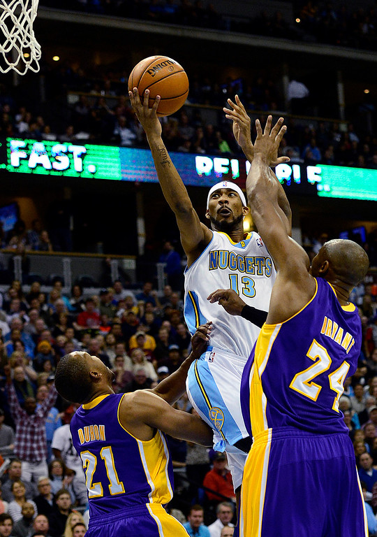 Description of . Denver Nuggets small forward Corey Brewer (13) drives on Los Angeles Lakers shooting guard Kobe Bryant (24) and point guard Chris Duhon (21) during the first half at the Pepsi Center on Wednesday, December 26, 2012. AAron Ontiveroz, The Denver Post