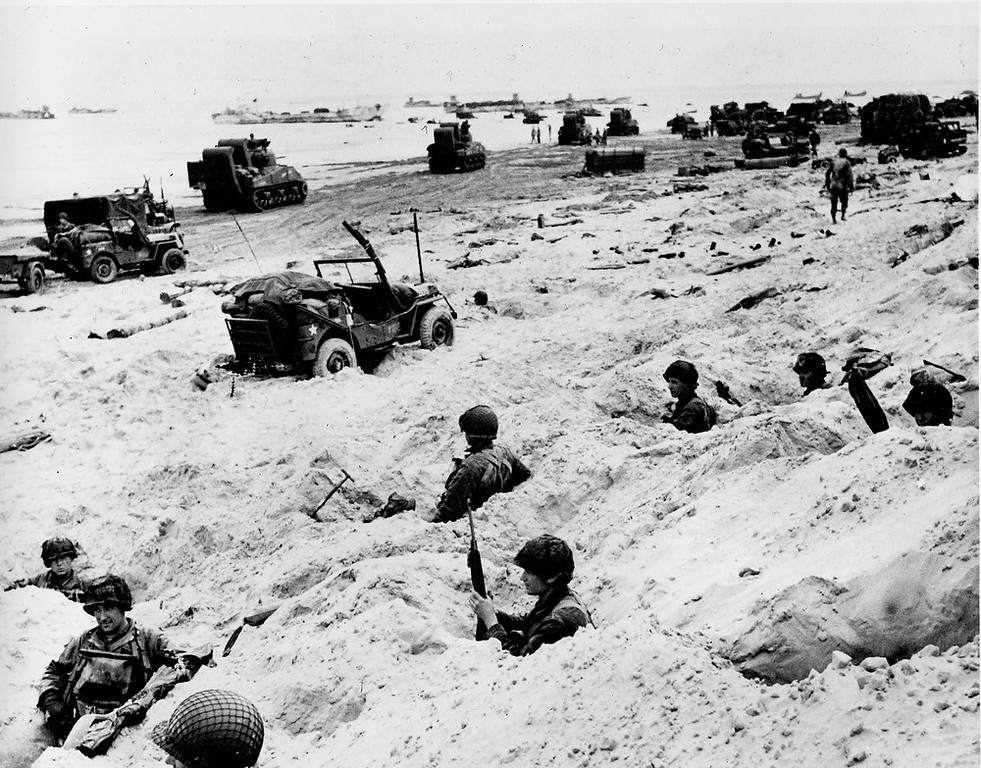 Description of . Sitting in the cover of their foxholes, American soldiers of the Allied Expeditionary Force secure a beachhead during  initial landing operations at Normandy, France, June 6, 1944. In the background amphibious tanks and other equipment crowd the beach, while landing craft bring more troops and material ashore. (AP Photo/Weston Haynes)