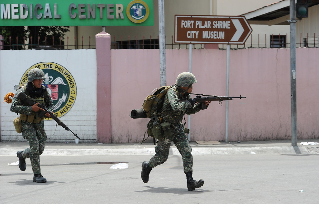 Description of . Government soldiers take cover from rebel's sniper fire during heavy fighting between rebels and government forces as the stand-off enter its fourth day in Zamboanga City, in southern island of Mindanao, on September 12, 2013.     AFP PHOTO/TED ALJIBE/AFP/Getty Images