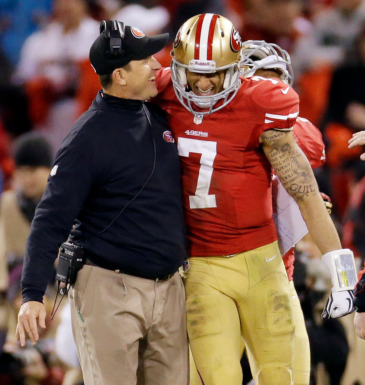 Description of . San Francisco 49ers head coach Jim Harbaugh celebrates with quarterback Colin Kaepernick (7) after Kaepernick's 56-yard touchdown run against the Green Bay Packers during the third quarter of an NFC divisional playoff NFL football game in San Francisco, Saturday, Jan. 12, 2013. (AP Photo/Ben Margot)