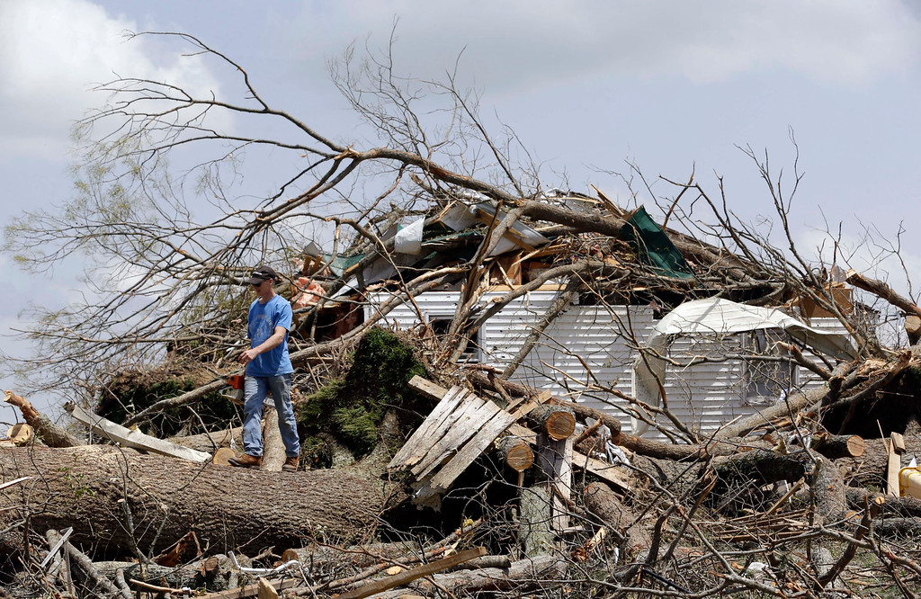 Description of . Mike Self helps to cut up trees Tuesday, April 29, 2014, that destroyed a home in Fayetteville, Tenn., when storms came through Monday.  On Sunday evening, roughly 15 tornadoes carved a path of destruction in the South and the country's midsection, according to estimates from the National Oceanic and Atmospheric Administration's Storm Prediction Center. On Monday, around 50 tornadoes ravaged the South, the agency said.  (AP Photo/Mark Humphrey)