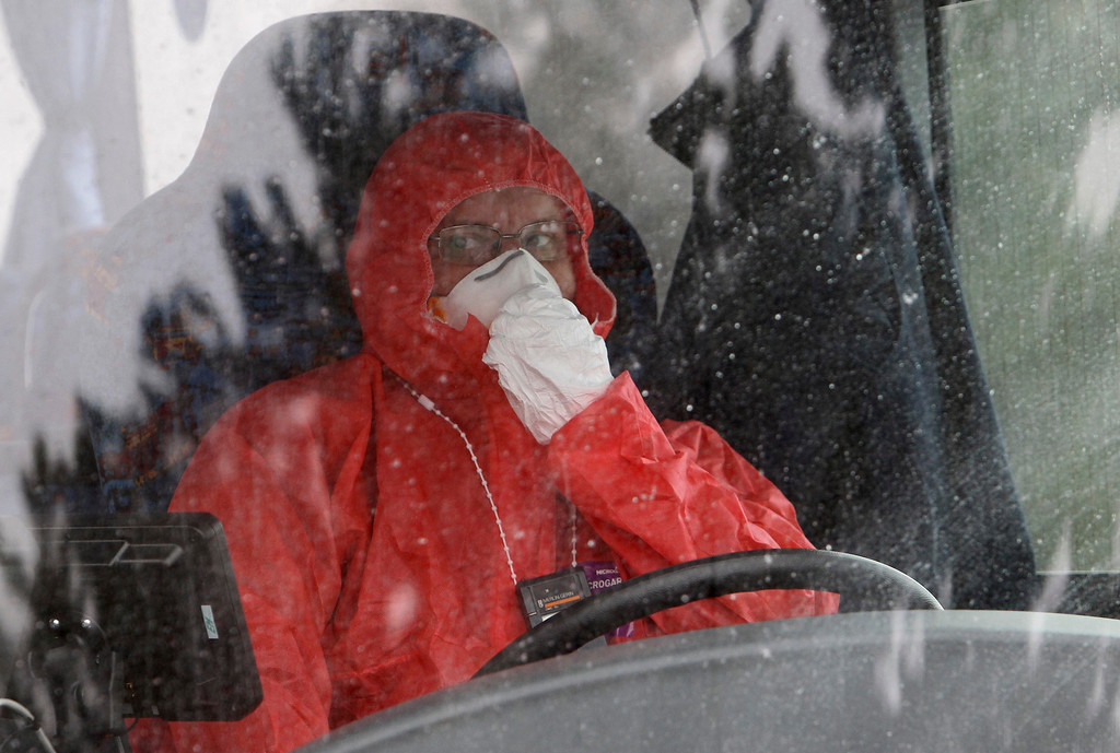 Description of . A worker wearing a protective suit adjusts his mask as he drives a bus during a nuclear accident simulation as part of a safety regulations exercise at Nuclear Power Plant Dukovany in Dukovany March 26, 2013.     REUTERS/David W Cerny