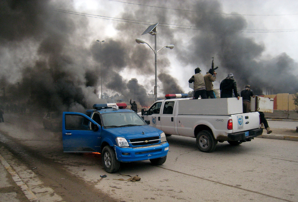 Description of . In this Wednesday January 1, 2014, file photo, al-Qaida fighters patrol in a commandeered police truck passing burning police vehicles in front of the main provincial government building, in Fallujah, 40 miles (65 kilometers) west of Baghdad, Iraq. With a new label - the Islamic State of Iraq and the Levant - the global terror network al-Qaida is positioning itself as a vanguard defending a persecuted Sunni community against Shiite-dominated governments across Syria, Lebanon and Iraq. The al-Qaida gains pose the most serious challenge to Prime Minister Nouri al-Maliki's Shiite-led government since the departure of American forces in late 2011. (AP Photo, File)