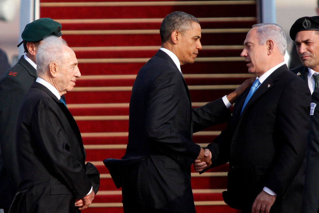 Description of . U.S. President Barack Obama (C) shakes hands with Israeli Prime Minister Benjamin Netanyahu (2nd R) as Israeli President Shimon Peres (L) looks on prior to Obama departing from Ben Gurion International Airport on March 22, 2013 in Lod' Israel.  (Photo by Lior Mizrahi/Getty Images)