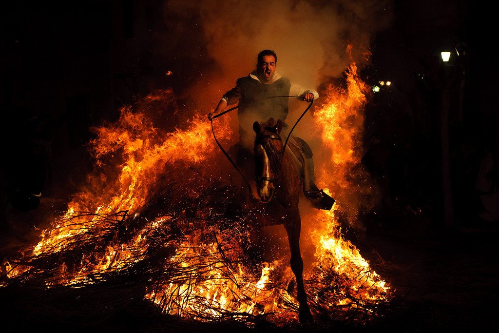 Description of . In this Jan. 16, 2012 file photo, a man rides a horse through a bonfire in San Bartolome de Pinares, Spain in honor of Saint Anthony, the patron saint of animals. On the eve of Saint Anthony's Day, hundreds ride their horses trough the narrow cobblestone streets of the small village of San Bartolome during the