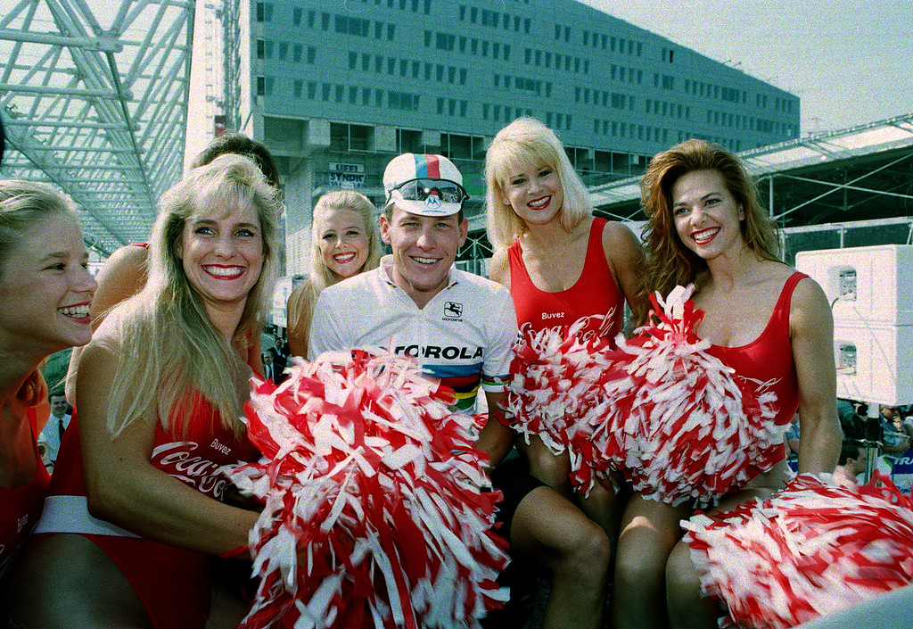 Description of . World champion cyclist Lance Armstrong of the United States poses with cheerleaders before start of the first stage of the Tour de France cycling race in Lille, northern France, Sunday, July 3, 1994. (AP Photo/Laurent Rebours)