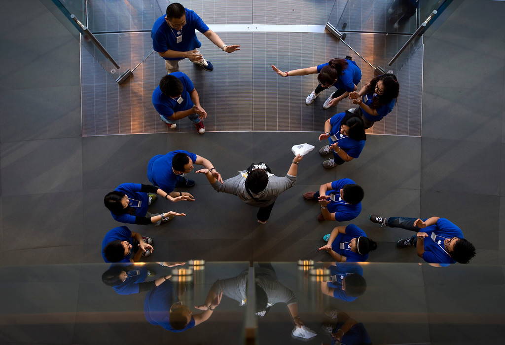 Description of . Chinese employees cheer a customer after he bought new iPhone at an Apple store in Wangfujing shopping district in Beijing on Friday, Sept. 20, 2013. Apple released the iPhone 5S and 5C models on Friday. (AP Photo/Andy Wong)