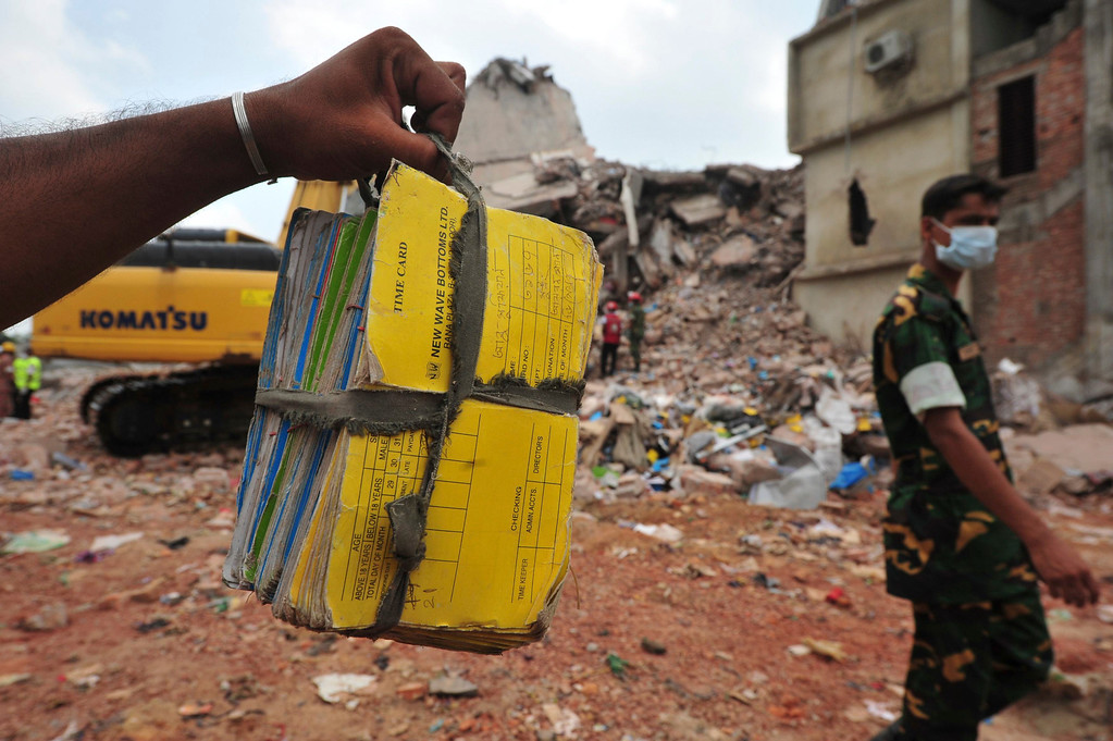 Description of . A rescue worker holds a a stack of files of a garment factory that was found from the rubble of the collapsed Rana Plaza building in Savar, around 30 km (19 miles) outside Dhaka April 30, 2013.  REUTERS/Khurshed Rinku