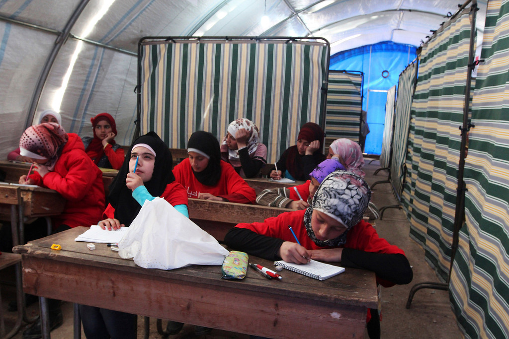 Description of . Syrian refugee girls attend class at the Bab Al-Salam refugee camp in Azaz, near the Syrian-Turkish border February 27, 2013. REUTERS/Hamid Khatib