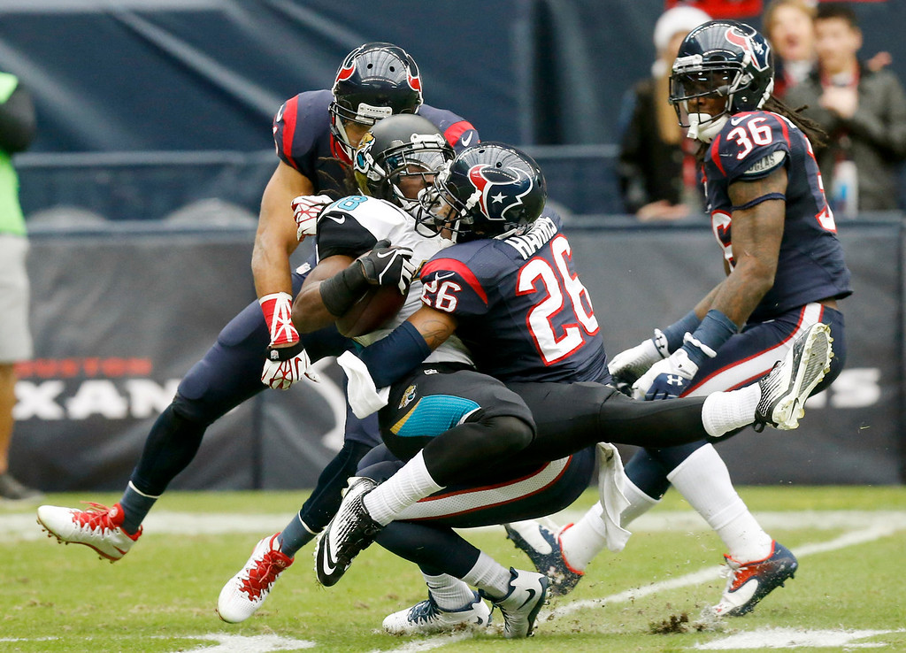 Description of . Houston Texans defensive back Brandon Harris (26) tackles Jacksonville Jaguars wide receiver Ace Sanders (18) during the first quarter an NFL football game Sunday, Nov. 24, 2013, in Houston. (AP Photo/Patric Schneider)