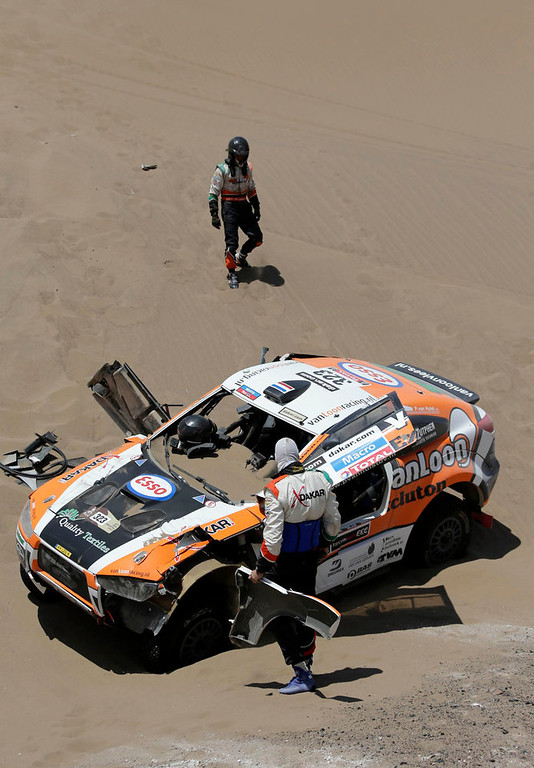 Description of . Netherlands Erik Van Loon (top) and co-pilot Marc Wams stand near their Mitsubishi after they crashed during the 6th stage of the Dakar Rally from Arica to Calama, January 10, 2013. Picture taken January 10, 2013. REUTERS/Jacky Naegelen