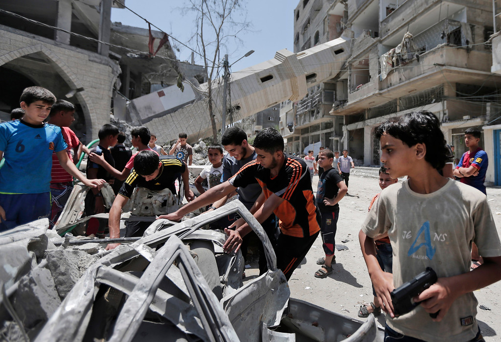 Description of . Palestinians inspect a destroyed car by a fallen minaret, in the background, of the Al-Sousi mosque, that was destroyed in an Israel strike, at Shati refugee camp in the northern Gaza Strip, Wednesday, July 30, 2014. (AP Photo/Lefteris Pitarakis)