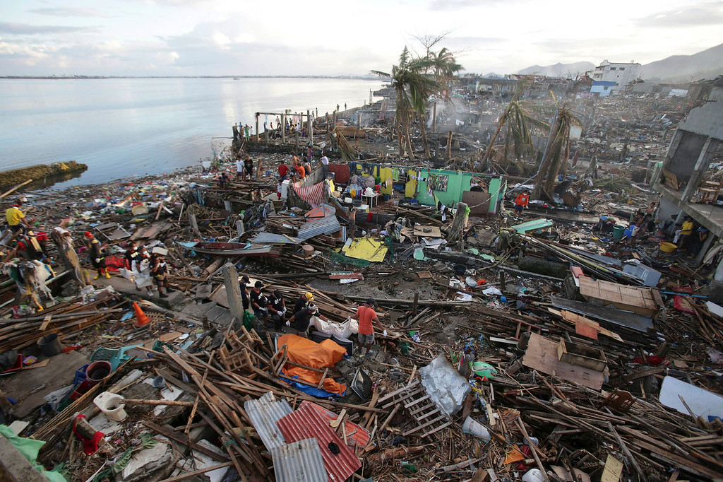 Description of . Filipino firemen and volunteers carry a body bag along the debris of damaged homes as workers continue search operations for missing people at Tacloban city, Leyte province, central Philippines on Sunday, Nov. 17, 2013. Typhoon Haiyan, one of the most powerful storms on record, hit the country's eastern seaboard Nov. 8, leaving a wide swath of destruction. (AP Photo/Aaron Favila)