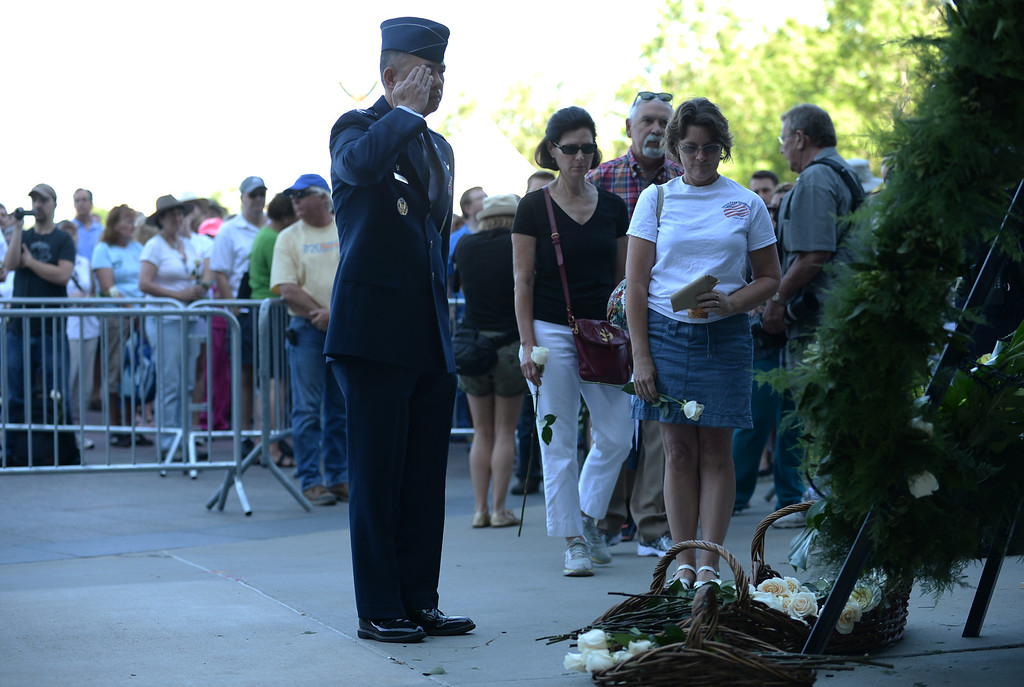 Description of . AURORA, CO. - July 20: An officer salutes the memorial during a day of remembrance at Aurora Municial Center. Aurora, Colorado. July 20, 2013. People gathered outside the Aurora Municipal Center to mark the first anniversary of the deaths of 12 people and the injury of at least 70 others in a mass shooting that forever changed an entire community. (Photo By Hyoung Chang/The Denver Post)