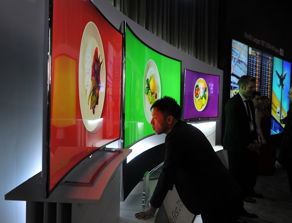 Description of . An attendee takes a close look at LG's 105 inch Ultra HD Oled TV,  at the 2014 International CES in Las Vegas, Nevada, January 8, 2014. The consumer electronics show, one of the largest in the world, runs from Jan 7-10. AFP PHOTO / Robyn BeckROBYN BECK/AFP/Getty Images