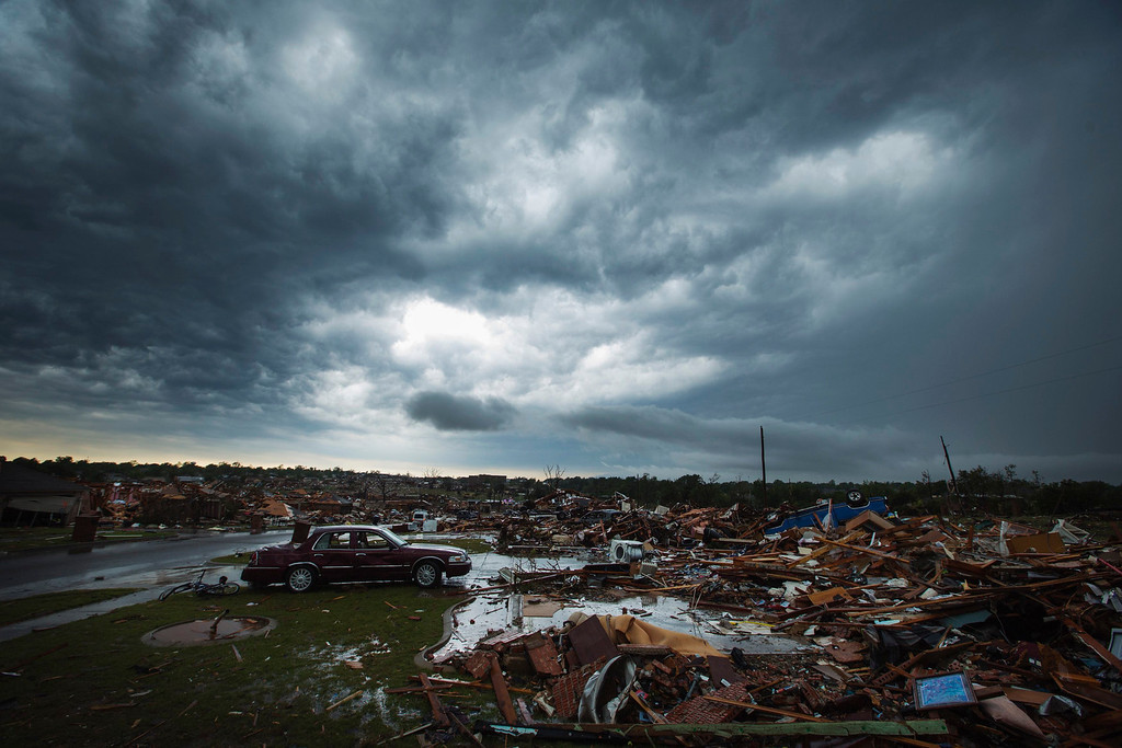 Description of . The clouds of a thunderstorm roll over neighborhoods heavily damaged in a tornado in Moore, Oklahoma, May 23, 2013. REUTERS/Lucas Jackson