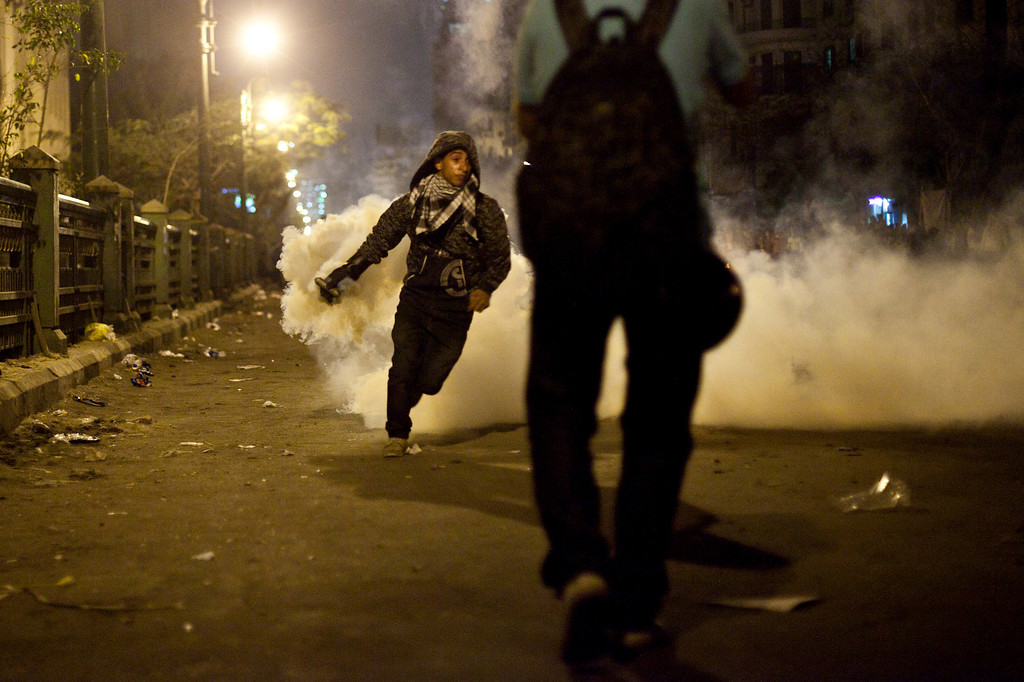 Description of . A protester throws away a tear gas canister fired by security forces in downtown Cairo, Egypt, Saturday, April 6, 2013. Police fired tear gas at hundreds of protesters outside the chief prosecutor's office Saturday in central Cairo after they tried to push on the building's doors demanding he resign.(AP Photo/Virginie Nguyen Hoang)