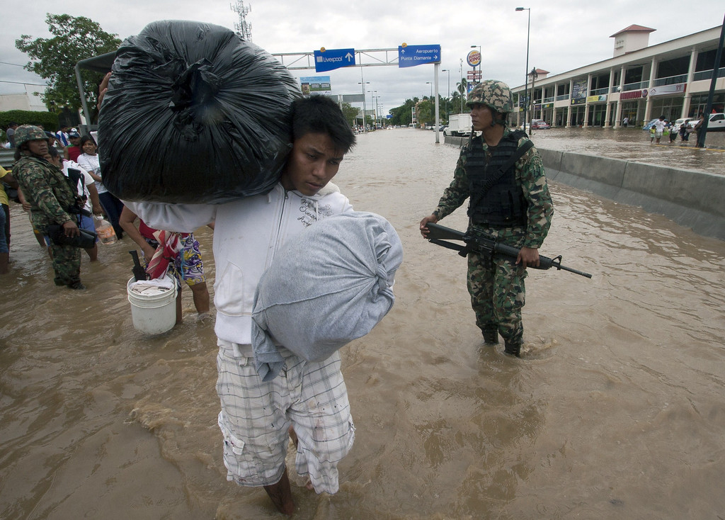 Description of . A resident carrying belongings wades through a flooded street in Acapulco, state of Guerrero, Mexico, on September 17, 2013 as heavy rains hit the country. Mexican authorities scrambled Tuesday to launch an air lift to evacuate tens of thousands of tourists stranded amid floods in the resort of Acapulco following a pair of deadly storms. The official death toll rose to 47 after the tropical storms, Ingrid and Manuel, swarmed large swaths of the country during a three-day holiday weekend, sparking landslides and causing rivers to overflow in several states. Pedro PARDO/AFP/Getty Images