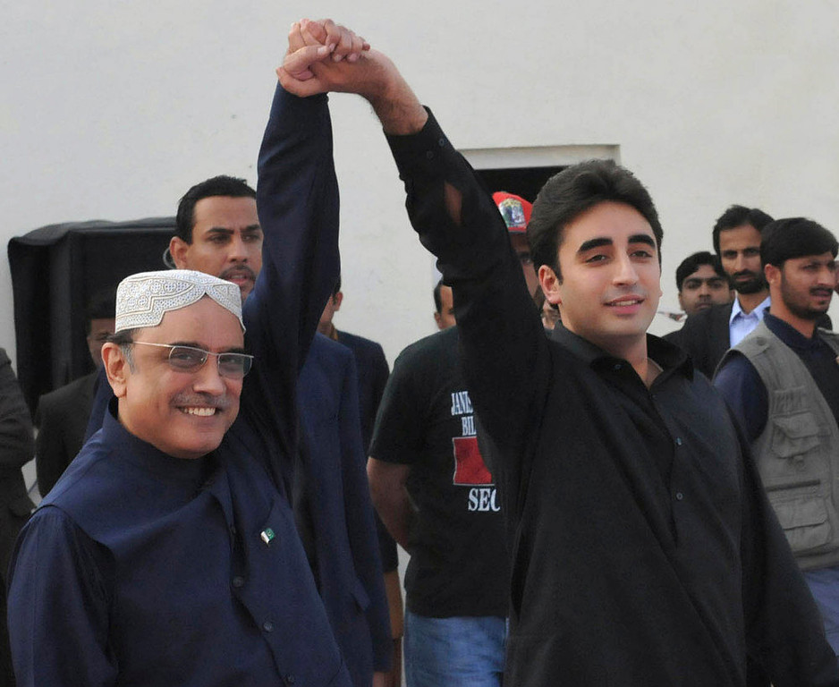 Description of . In this handout photo released by the Press Information Department, Pakistan's President Asif Ali Zardari, left, raises the hand of his son  Bilawal Bhutto Zardari during a rally to mark the fifth anniversary of Pakistan's assassinated leader Benazir Bhutto in Garhi Khuda Baksh, Larkana, on Thursday, Dec. 27, 2012 in Pakistan. Bilawal Bhutto Zardari,  24-year-old son of Bhutto launched his political career Thursday with a fiery speech before thousands of cheering supporters observing the fifth anniversary of his mother's assassination. (AP Photo/Press Information Department)