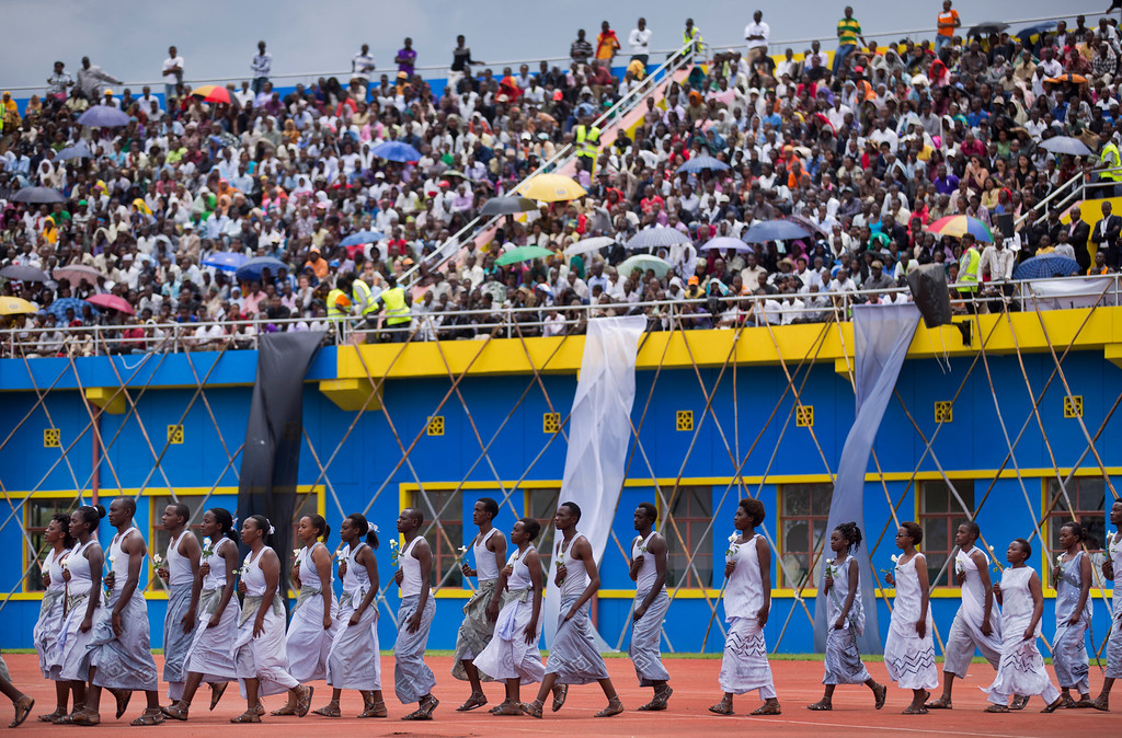 Description of . Performers re-enacting some of the events enter a public ceremony to mark the 20th anniversary of the Rwandan genocide, at Amahoro stadium in Kigali, Rwanda Monday, April 7, 2014.  (AP Photo/Ben Curtis)
