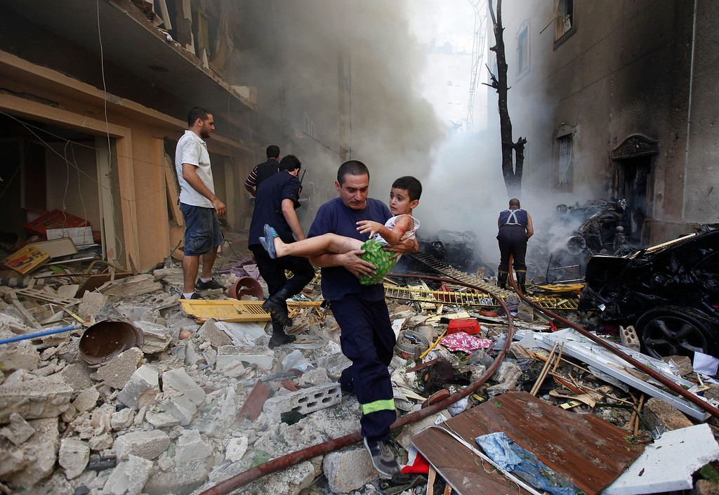Description of . In this Oct. 19, 2012 file photo, a Lebanese rescue man, carries an injured boy at the scene of an explosion in the mostly Christian neighborhood of Achrafiyeh, Beirut, Lebanon. A car bomb ripped through eastern Beirut, shearing the balconies of off residential buildings and sending bloodied victims pouring out into the streets in the most serious blast this city has seen in years. (AP Photo/Hussein Malla, File)