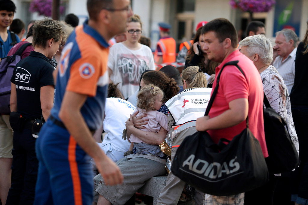 Description of . A woman holds a child amidst rail workers and Red Cross workers on the site of a train accident in the railway station of Bretigny-sur-Orge, Friday, July 12, 2013 near Paris. (AP Photo/Kenzo Tribouillard, POOL)