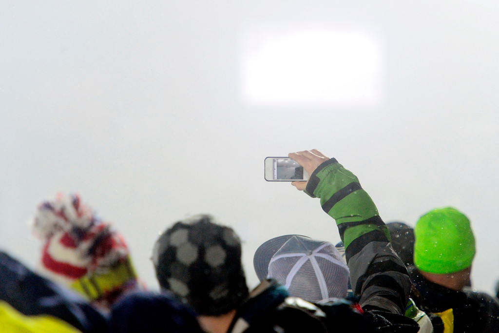 Description of . ASPEN, CO - JANUARY 26: A fan attempts to photograph through the snowfall during the women's snowboard superpipe final. X Games Aspen Buttermilk Mountain Aspen January 26, 2013 (Photo By AAron Ontiveroz / The Denver Post)