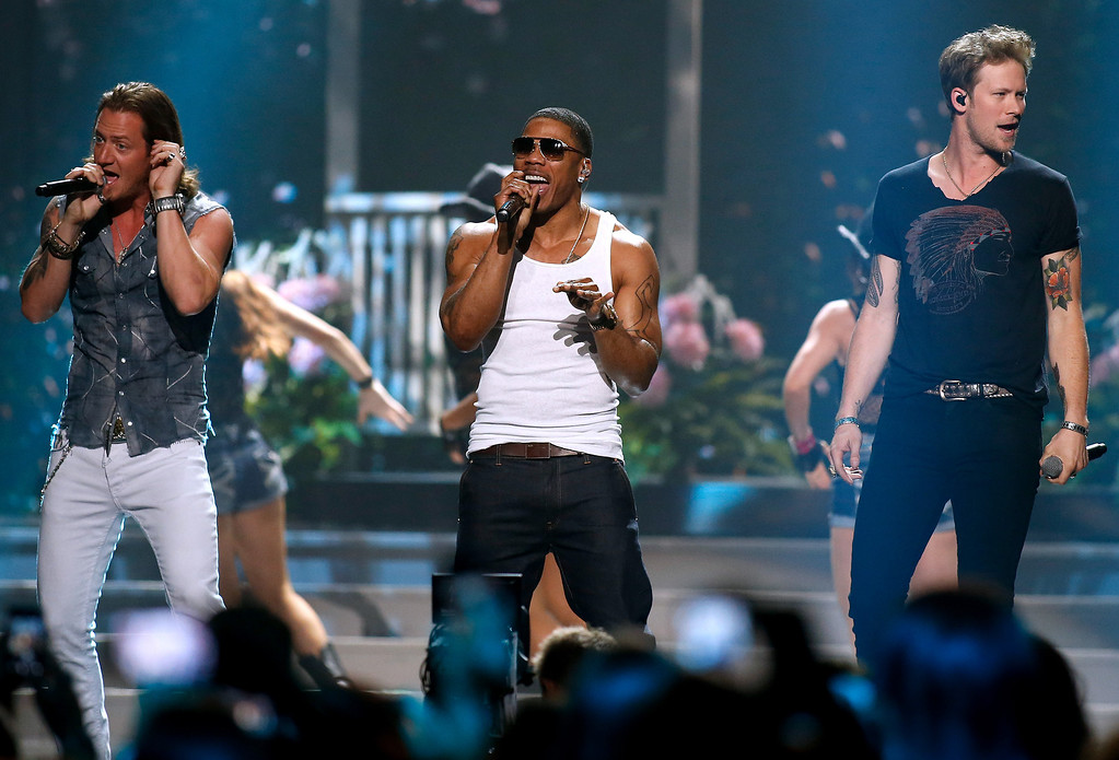 Description of . Tyler Hubbard, left, and Brian Kelley, right, of Florida Georgia Line perform with Nelly, center, during the Miss USA 2014 pageant in Baton Rouge, La., Sunday, June 8, 2014. (AP Photo/Jonathan Bachman)