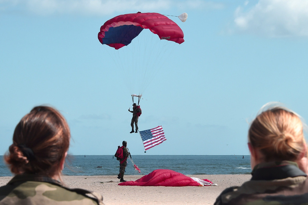 Description of . French 1st RCP paratrooper carrying U.S. flag is seen over Sword beach in Ouistreham, northern France, on June 5, 2014, a day before the start of the D-Day commemorations. / DAMIEN MEYERDAMIEN MEYER/AFP/Getty Images