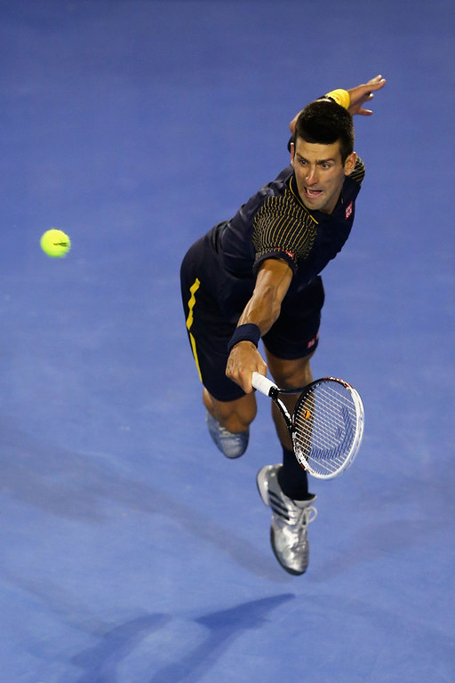 Description of . Novak Djokovic of Serbia plays a backhand in his men\'s final match against Andy Murray of Great Britain during day fourteen of the 2013 Australian Open at Melbourne Park on January 27, 2013 in Melbourne, Australia.  (Photo by Quinn Rooney/Getty Images)