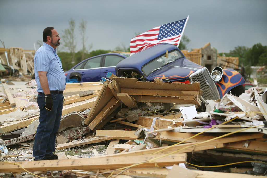 Description of . Dan Wassman looks at the debris at the homesite of his son, also named Dan Wassum, who was killed when a tornado destroyed his home April 29, 2014 in Vilonia, Arkansas. Deadly tornadoes ripped through the region April 27, leaving more than a dozen dead.  (Photo by Mark Wilson/Getty Images)