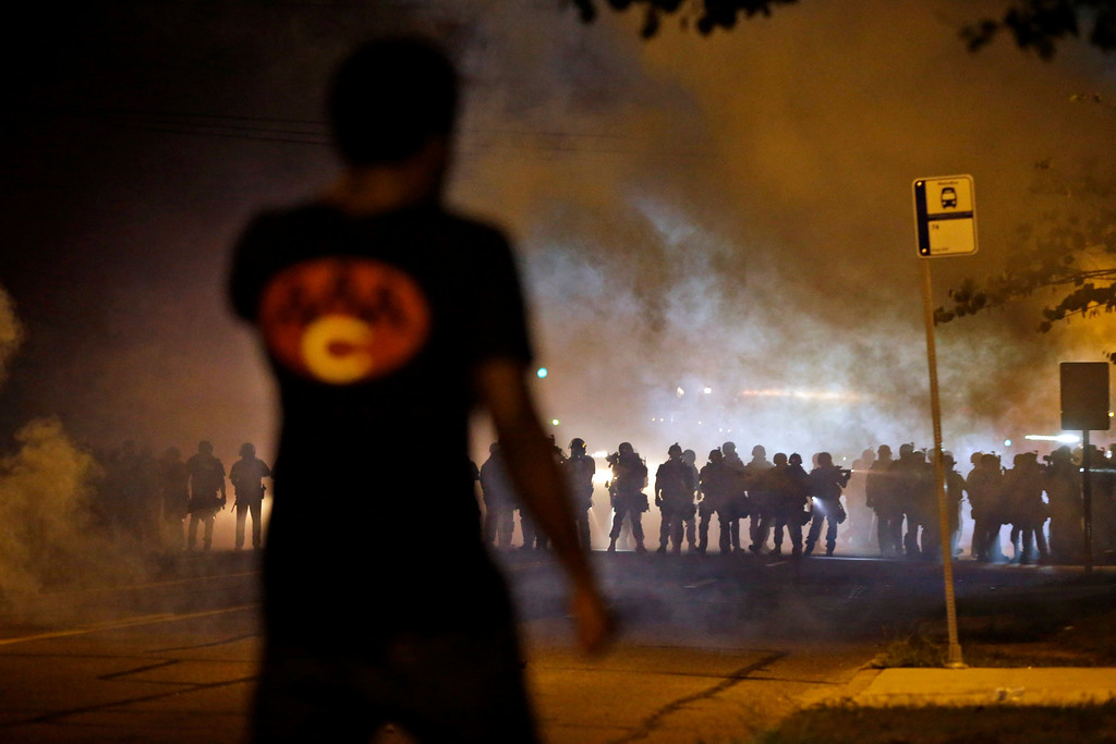Description of . A man watches as police walk through a cloud of smoke during a clash with protesters Wednesday, Aug. 13, 2014, in Ferguson, Mo. (AP Photo/Jeff Roberson)