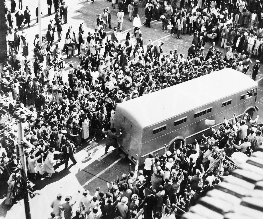 Description of . Crowds cheer as a police van brings prisoners to the Drill Hall, in Johannesburg, South Africa, Dec. 31, 1956, for the start of the 'Treason Trial'. One man has climbed onto the step of the van top shout encouragement to the inmates. Nelson Mandela was among the people arrested and standing trial. (AP Photo)