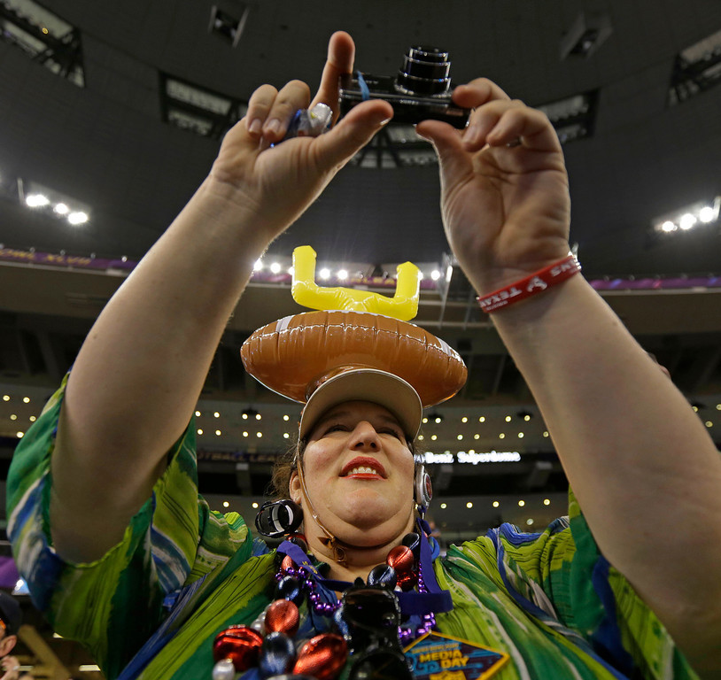 Description of . NFL football fan Karen Vine Fuller of Houston wearing a goalpost hat shoots photos of the San Francisco 49ers during media day for the NFL Super Bowl XLVII football game Tuesday, Jan. 29, 2013, in New Orleans. (AP Photo/Gerald Herbert)