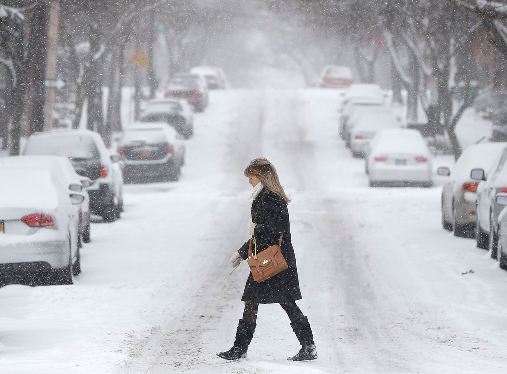 Description of . A pedestrian walks through morning snow, Thursday, Jan. 2, 2014, in Albany, N.Y. Snow and bone-chilling temperatures are greeting morning commuters across New York on the first work day of 2014, with some upstate areas expected to get more than a foot of snow by the weekend. (AP Photo/Mike Groll)